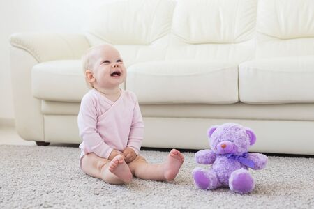 childhood, babyhood and children concept - happy little baby girl sitting on floor at home Reklamní fotografie