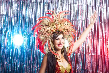 Carnival, dancer and holiday concept - Beauty brunette woman in cabaret suit and headdress with natural feathers and rhinestones.