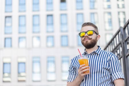 Bottom view portrait of a stylish young hipster male in mirror glasses with juice on the background of the business center. Urban holiday at the weekend concept. Banco de Imagens