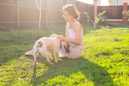 Young woman with her jack russell terrier dog playing on the grass outside