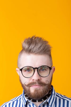 Young positive trendy man hipster with a mustache beard and necklace in shirt posing on a yellow background with copy space. Concept of rock and subculture.