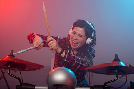 Music, drum and hobby concept - young woman playing the electronic drum set at the club 版權商用圖片