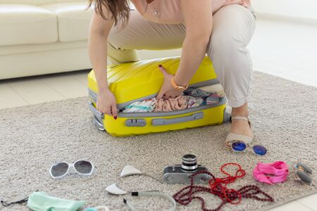 Trip, travel and holidays concept - woman trying to close her suitcase 版權商用圖片