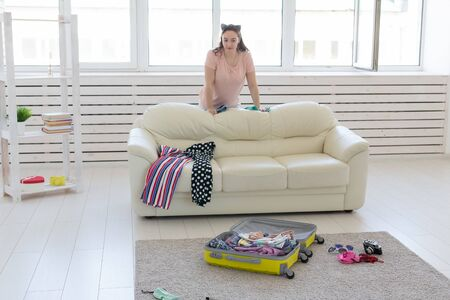 Holidays, voyage and travel concept - Young Woman collects a suitcase at home in the bedroom, a lot of things, vacation and yellow suitcase