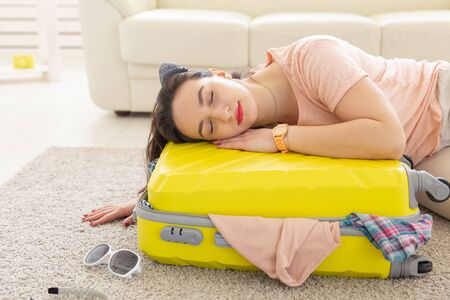 Trip, travel and holidays concept - woman is tired of collecting things for the trip 版權商用圖片