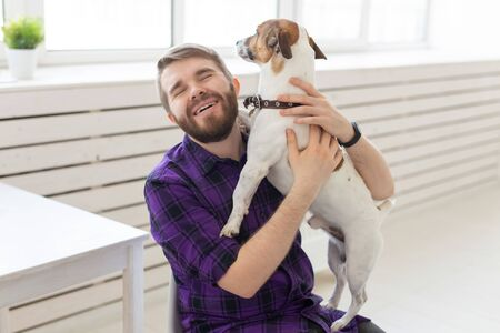 people, pets and home concept - young man playing with jack russell terrier puppy