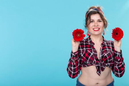 pin-up and flower concept - pretty young woman with gerberas on blue background with copy space