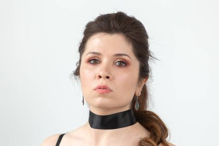 Close-up portrait of a charming pensive young beautiful woman in black clothes with a black ribbon around her neck. Фото со стока