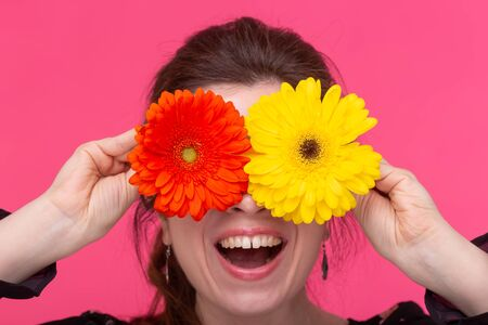 Flowers, emotions and people concept - woman closed her eyes with gerberas on pink background 写真素材