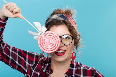 candy, fashion and fun concept - pin-up woman closed her eye by lollipop on blue background