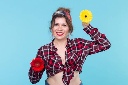 Summer, pin-up and fun concept - pretty woman with gerberas over the blue background