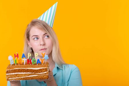 Crazy cheerful young woman in paper congratulatory hat holding cakes happy birthday standing on a yellow background with copy space. Jubilee congratulations concept.