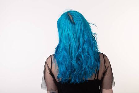 People and fashion concept - Beautiful woman with blue hair posing over white background, back view