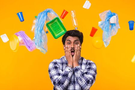 Environmental pollution, plastic recycling problem and ecology problem concept - Terrified Indian man on yellow background with trash