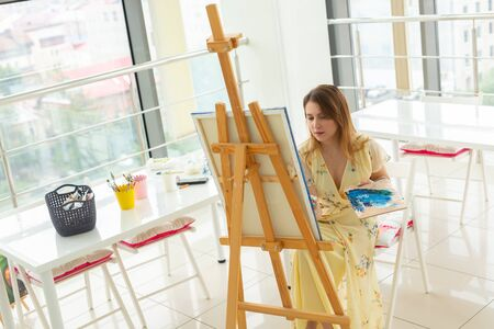 School of art, college of arts, education for group of young students. Happy young woman smiling, girl learning to paint. Stock fotó