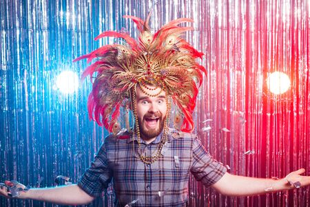 Fun, holiday, april fools day and funny people concept - Portrait of a young man wearing masquerade hat.