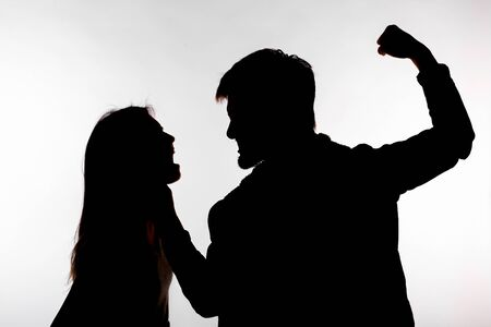 Domestic violence and abuse concept - Silhouette of man beating defenseless woman Imagens