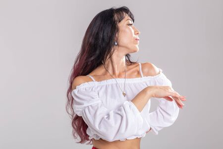 Latin dance, bachata lady, jazz modern and vogue dance concept - Beautiful young woman dancing on white background with copy space