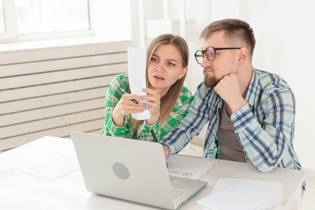 Upset husband and wife consider the total costs of payments and purchases made over the past month. The concept of low standard of living of students. Imagens