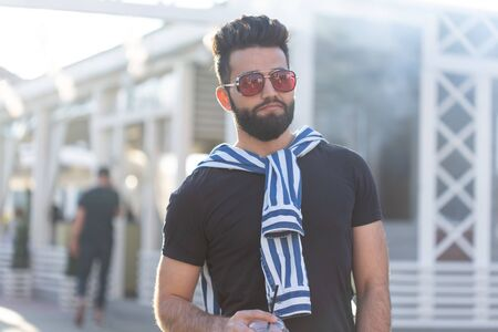 Portrait of a stylish young hipster arab male with juice. Urban holiday at the weekend concept. Stockfoto