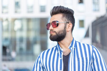 Portrait of cheerful positive stylish student guy in glasses with a mustache and beard outdoors. The concept of successful cheerful people.