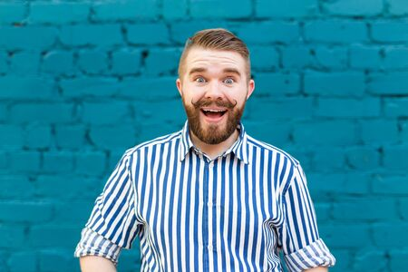 Portrait of a young positive stylish smiling guy with a mustache and beard against the background of a blue brick wall. Vacation concept in the city.