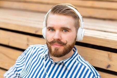 Close-up portrait of a serious young student guy listening to his favorite online radio using headphones while sitting in a park on a sunny warm summer day. Stockfoto