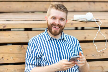 Happy young male hipster student with a mustache and beard writing sms message to his friends resting after studying in the park sitting on a wooden bench with a tablet and headphones