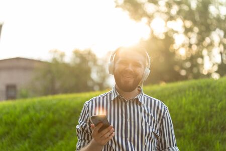 Positive young male hipster listens to your favorite online radio using smartphone headphones and high-speed wireless internet in the park on a sunny warm summer day. Stockfoto