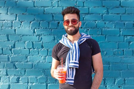 Cute stylish arab young male hipster with a mustache and a beard and wearing glasses drinking juice with a straw. Summer vacation concept. Stockfoto