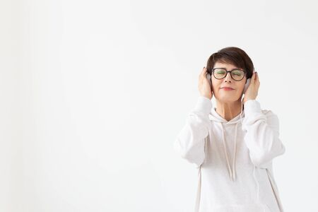 Pretty keen middle-aged woman in glasses and a white sweater listens to her favorite music with headphones on a white background with copy space. Online radio and music subscription concept.