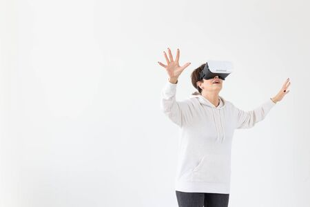 Positive pretty middle-aged woman in a white sweater watching a movie with glasses of virtual reality. The concept of futurism and new technologies.