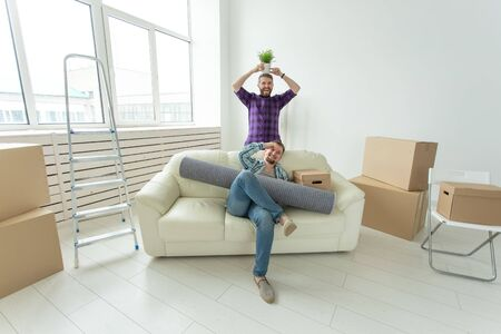 Two student male friends holding their things in their hands sitting in the living room of a new apartment. Housewarming concept Stock Photo