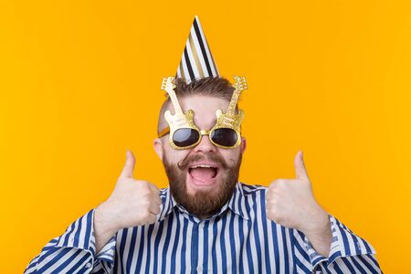 Crazy young positive hipster guy with a beard laughs happily on a yellow background. The concept of holidays and sales Stockfoto