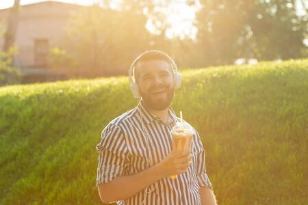 Side view of a stylish young man with a beard holding a milkshake and admiring the city views walking in the park on a warm summer day. The concept of rest and relaxation. Stockfoto