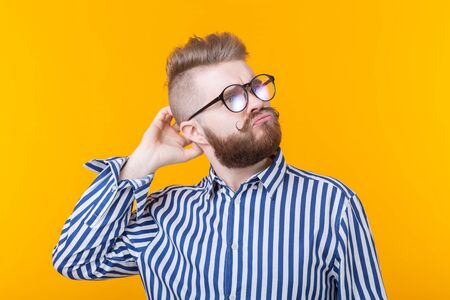 Cute intelligent young man with a beard and with glasses poses on a yellow background and thinks about something. The concept of a difficult choice.