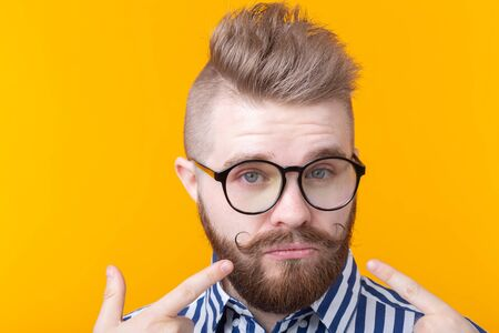Charming confident young fashion hipster man with glasses and a beard shows on himself posing over a yellow background. Place for advertising. The concept of self-confidence and success. Stockfoto