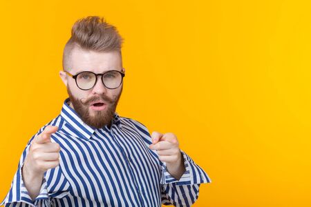 Funny young man with a mustache and a beard and glasses shows on you on a yellow background with copy space. Concept of non-standard advertising.