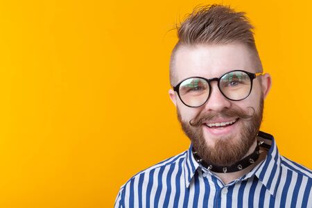 Young positive trendy man hipster with a mustache beard and fetish necklace in shirt posing on a yellow background with copy space. Concept of rock and subculture. Stockfoto