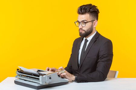 Side view of a young charming male businessman in formal attire and glasses typing on a typewriter text. Concept of business affairs and ideas.