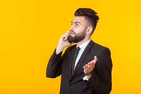 Cute young man with a beard in formal clothes talking on the phone posing on a yellow background. Concept of an informal meeting and business deal.