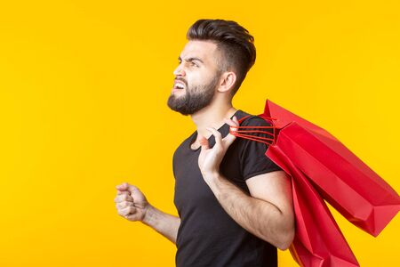 Side view of an upset young bearded stylish hipster man holding shopping bags posing on a yellow background. Concept of superfluous purchases.