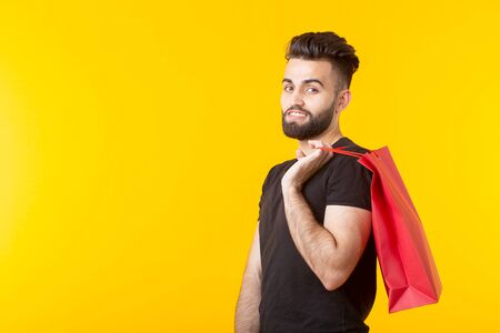Man is holding red shopping bags on a yellow background. The concept of shopping in the supermarket and gifts. Advertising space. Stockfoto