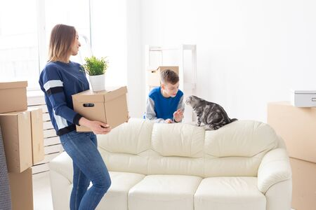 Slim positive young single mother and a cute boy son arrange things and communicate with their scottish fold cat. Housewarming and relocation concept