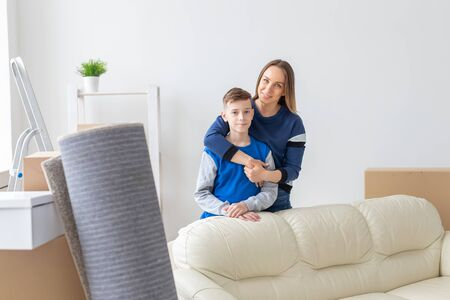 Positive smiling single mother and charming son are posing standing in a new bright comfortable apartment. The concept of moving and mortgages for new housing.