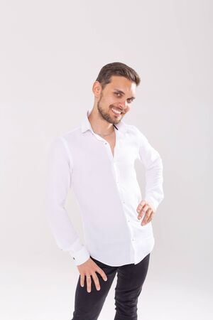 Portrait of handsome happy young man in casual shirt standing against white background