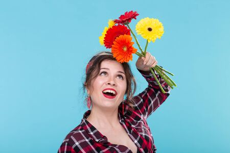 Beautiful positive young woman in a plaid shirt and a bandage sniffing beautiful bright gerbera flowers posing over a blue background. Concept of gifts and greetings.