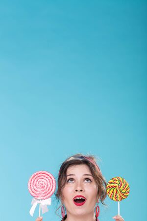 Diet and junk food concept - pin-up woman looking up on blue background with copy space