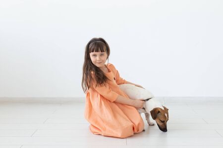 Little girl with dark hair plays with her beloved dog while sitting on the floor in a peach dress against background of white wall. Concept of taking care of children and animals. Advertising space.