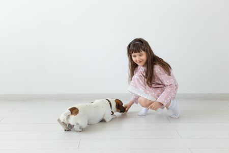 Cheerful little girl in a blue dress playing with her beloved dog Jack Russell Terrier. Friendship concept of children and dogs. Advertising space Stock Photo - 129600831